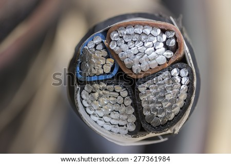 Cross section of black industrial underground cable on large wooden reel. Four core al cable. Selective focus and shallow dof. - stock photo