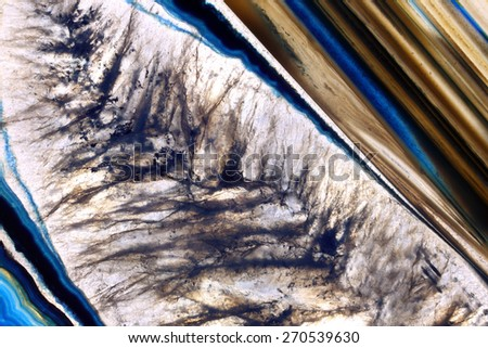 Cross-section of blue, white, black and gold natural quartz crystal. The translucent nature of the crystal allows visibility of the layers of color, formations and veins beneath the surface. - stock photo