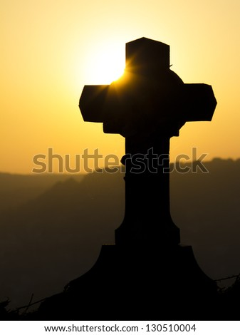 Cross silhouette against a sunset - stock photo