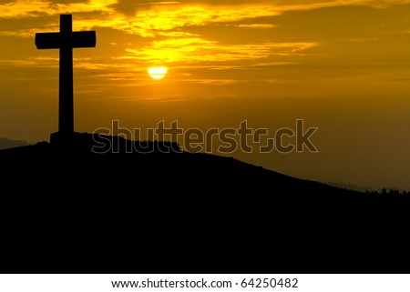 Cross silhouette in the top of a mountain at sunset
