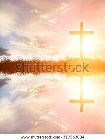 cross silhouette on the mountain at sunset with water reflection - stock photo
