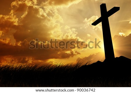 cross silhouette with the sunset as background - stock photo