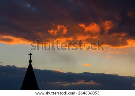 cross silhouette with the sunset as background and red clouds