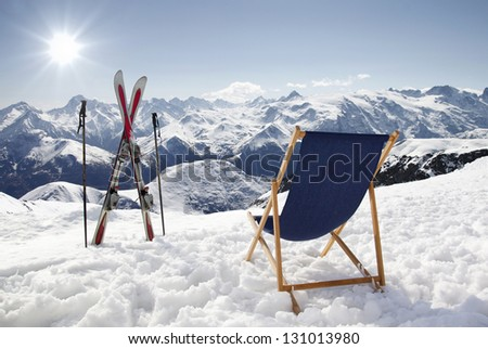 Cross ski and Empty sun-lounger at mountains in winter, France High mountain - stock photo