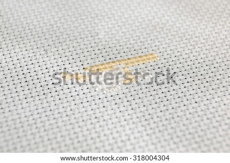 cross-stitch on a white canvas by light orange and white thread close-up - stock photo