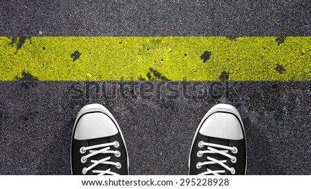 Cross the yellow line ? Concept illustration showing shoes in front of a yellow line. - stock photo