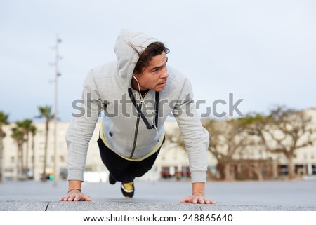 Cross-training at early morning outdoors, young man doing push ups looking away  - stock photo