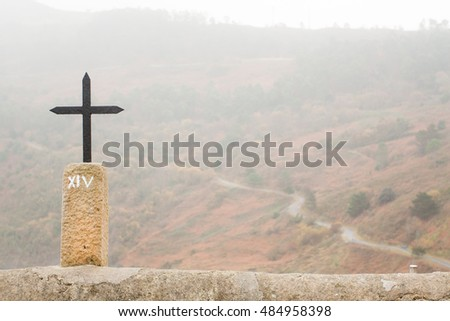 Cross with a road in a forest in the background during a misty day