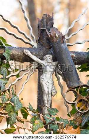 Cross with crucified Jesus Christ at cemetery  - stock photo