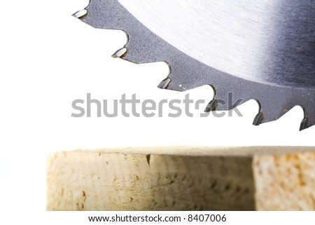 Crosscut timber in focus with circular saw teeth above - stock photo