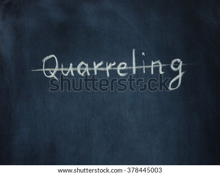 crossed out the word Quarreling on black chalkboard. Psychology concept