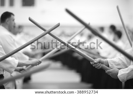 Crossed wooden swords in hands of martial arts' practitioners - stock photo
