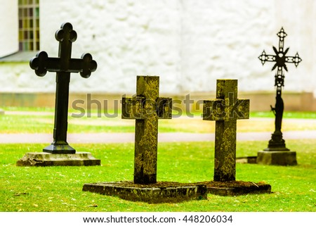 Crosses on a churchyard with part of the church in the background.