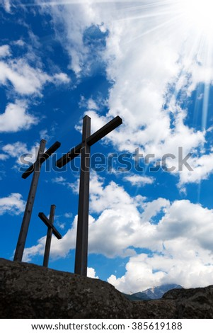 Crosses Silhouette against Blue Sky / Silhouette of three crosses against a blue sky with clouds and sun rays. Carisolo Trentino Italy - stock photo