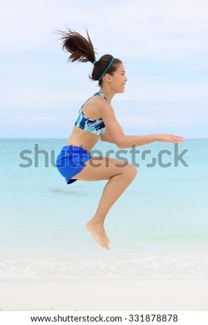 Crossfit fitness Asian woman on beach doing jump squat plyometric training exercises by jumping and touching knees as part of a full body core workout and active lifestyle. - stock photo