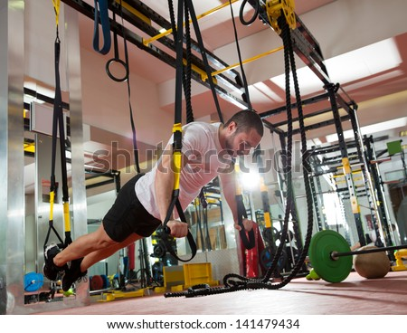 Crossfit fitness TRX push ups man workout at gym - stock photo