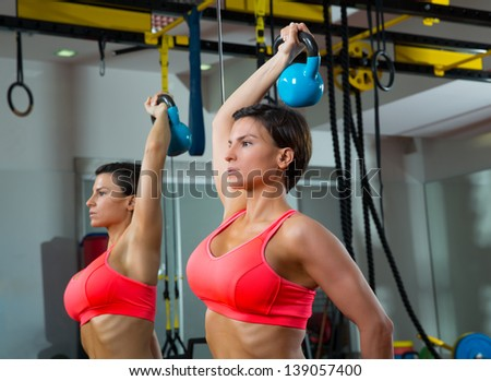 Crossfit fitness weight lifting Kettlebell woman at mirror workout exercise at gym - stock photo