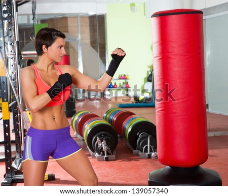 Crossfit fitness woman boxing with red punching bag at gym - stock photo