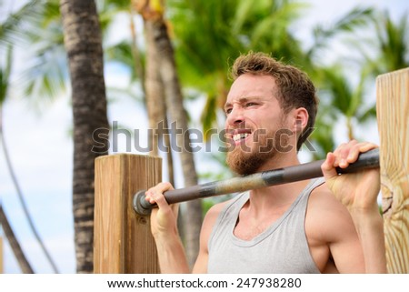 Crossfit man working out pull-ups on chin-up bar. Portrait of bearded fit young man cross training arms on horizontal bars outside on outdoor gym in summer. - stock photo