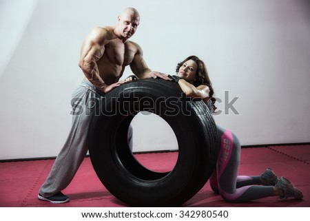 CrossFit training. Woman and man with tire. - stock photo
