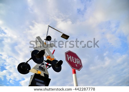 Crossing gate sign with electric poles, warning in Thai train railway - stock photo