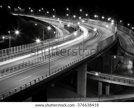 Crossing highway with car and lamp lights at night - stock photo