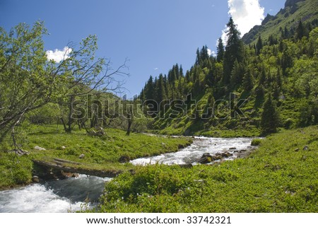 Crossing on mountain small river - stock photo