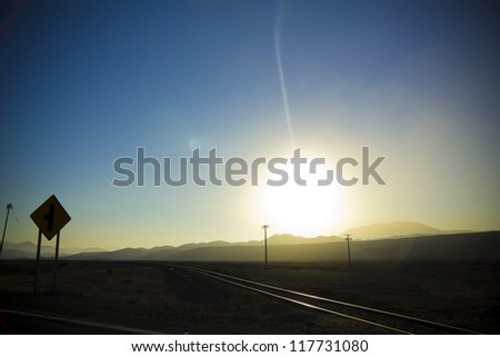 Crossing railroad tracks, sunset in the Andes, Atacama, Chile. Between Copiapo and Atacama, is one of the new routes Paris Dakar - stock photo