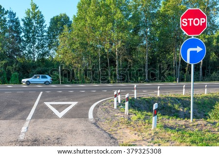 crossroads of rural road and moving car - stock photo