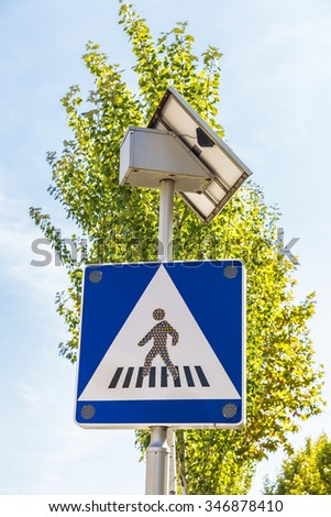 Crosswalk signal that is powered by solar energy with its own solar panel - stock photo