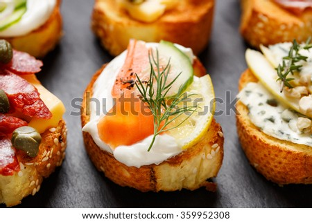 Crostini with addition of creamy cheese, smoked salmon, cucumber, lemon and dill. Delicious appetizer with slices of  baguette and various toppings on black background - stock photo
