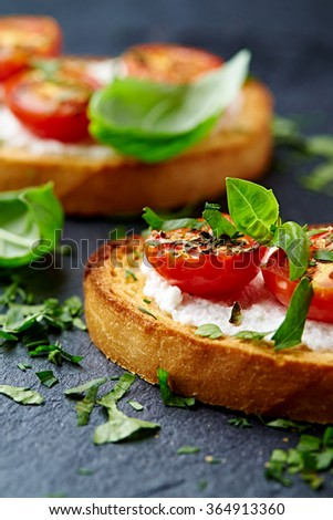 Crostini with cherry tomatoes and ricotta  - stock photo
