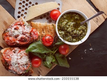 crostini with fresh cherry tomatoes,pesto and parmesan - stock photo