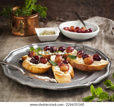 Crostini with goat cheese, grapes and rosemary. - stock photo