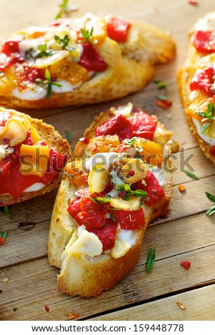 Crostini with grilled bell pepper, goat cheese, garlic and herbs - stock photo