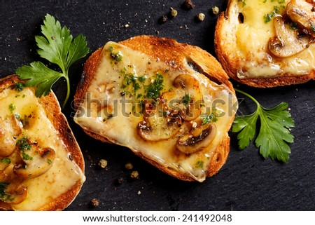 Crostini with melted cheese, mushrooms and fresh parsley - stock photo