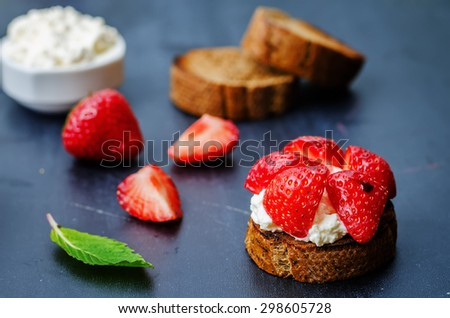 crostini with ricotta and strawberries on a black background. the toning. selective focus - stock photo