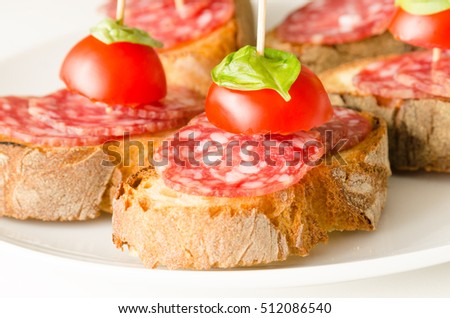 Crostini with salami, tomato and basil, Italian appetizers