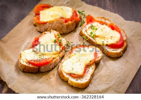 Crostini with tomato, cheese and thyme on parchment paper. Party appetizer or a snack. Selective focus - stock photo