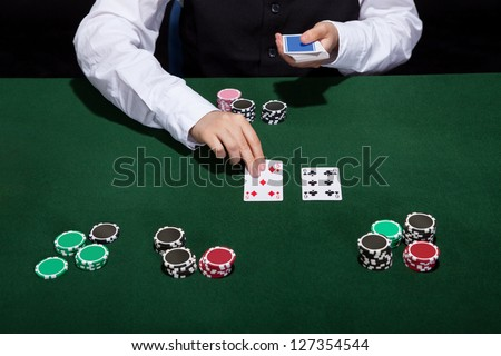 Croupier dealing cards in a poker game placing them face up on the green baize of the gaming table - stock photo