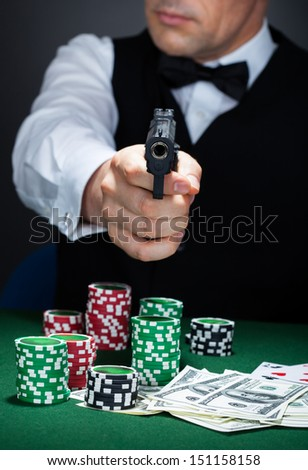 Croupier with stack of token chips and banknote on table aiming with a gun