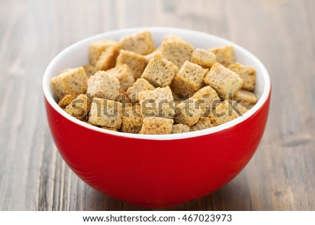 croutons in red bowl on brown wooden background