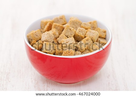 croutons in red bowl on white wooden background