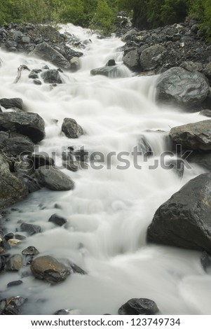 Crow Pass Creek rushes down a mountain side in the Chugach National Forest near Girdwood, Alaska - stock photo