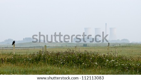 Crow sitting on fence with nuclear power plant in the background
