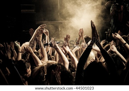 Crowd at a concert, audience raising hands up - stock photo