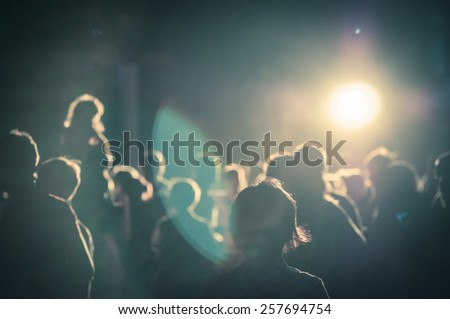 crowd at a concert in a moody light noise added - stock photo