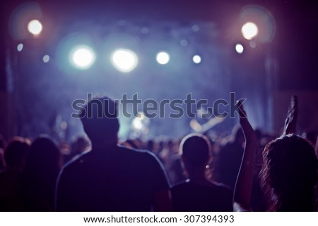 crowd at a concert in a vintage light noise added