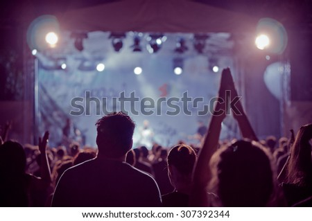 crowd at a concert in a vintage purple light noise added