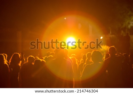crowd at a concert in a yellow light. grain added - stock photo